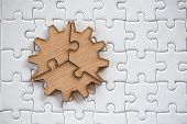 Three Brown Pieces Of Puzzle On A White Jigsaw Background, Last Piece Of Jigsaw Puzzle To Complete T poster