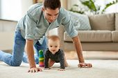 family, fatherhood and parenthood concept - happy little baby girl with father at home crawling on f poster