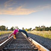 picture of bending over backwards  - Young attractive female Arching Back over Railroad tracks - JPG