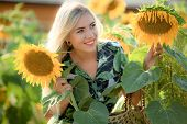 Beautiful Young Woman Posing Near Sun Flowers. Summer Portrait At The Field. Happy Woman In Beauty F poster