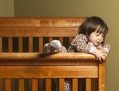 picture of bassinet  - Toddler in bedroom climbing out of her crib - JPG
