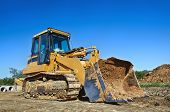 stock photo of power-shovel  - Yellow bulldozer at a construction site against blue sky - JPG