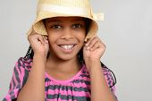 image of cornrow  - African Girl being silly with hat on a grey background - JPG
