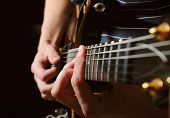 stock photo of guitarists  - close up shot of strings and guitarist hands playing guitar over black  - JPG