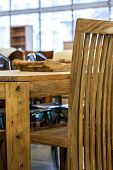 pic of thrift store  - A brown chair by a wooden table - JPG