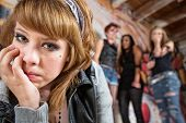pic of shy woman  - Sad European young woman being teased by group of teenagers - JPG