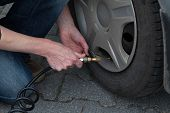 pic of pry  - A man is pumping a flat tyre
