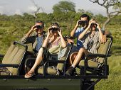foto of  jeep  - Group of tourists sitting in jeep and looking through binoculars - JPG