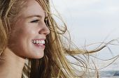 image of windswept  - Closeup profile of a smiling young woman looking away with blond hair blowing in wind - JPG