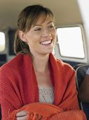 stock photo of campervan  - Happy young woman wrapped with blanket in campervan - JPG