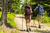 Sporty hikers on path with trekking poles