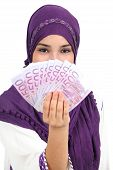stock photo of hijabs  - Beautiful islamic woman wearing a hijab showing a lot of banknotes isolated on a white background - JPG