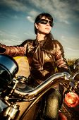 image of biker  - Biker girl in a leather jacket on a motorcycle looking at the sunset - JPG