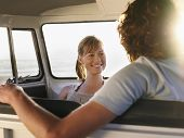 stock photo of campervan  - Smiling young woman looking at boyfriend in campervan - JPG