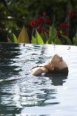 stock photo of infinity pool  - Young woman swimming in infinity pool - JPG