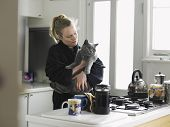 Happy young woman in bathrobe holding cat at domestic kitchen