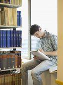 image of shelving unit  - Young male student sitting on windowsill in library and writing notes - JPG