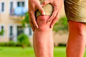 stock photo of short legs  - man holding hands sore knee - JPG