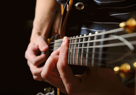 image of string instrument  - close up shot of strings and guitarist hands playing guitar over black  - JPG