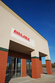 stock photo of commercial building  - retal space for rent with available banner on it - JPG