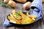 picture of potato-field  - Baked potato wedges with rosemary in an iron pan, raw potatoes in the background