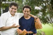 stock photo of teenage boys  - Hispanic father with African American teenage son holding baseball and glove - JPG