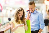 foto of mall  - Happy young couple with bags in shopping mall - JPG