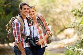 stock photo of couples  - happy young couple hiking in mountain - JPG