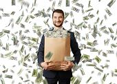 picture of heavy bag  - smiley young businessman holding paper bag with money under dollar - JPG