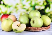 image of picking tray  - Juicy apples on woven tray on wooden table on nature background - JPG