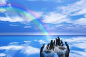 image of end rainbow  - Rainbow ends in cupped hands in serene landscape - JPG