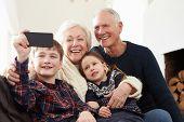 pic of grandparent child  - Grandparents And Grandchildren Sitting On Sofa Taking Selfie - JPG