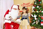 stock photo of letters to santa claus  - Little cute girl giving letter with wishes to Santa Claus near Christmas tree at home - JPG