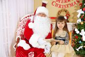 stock photo of letters to santa claus  - Little cute girl giving letters with wishes to Santa Claus near Christmas tree at home - JPG