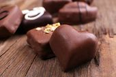 pic of foreground  - Various of sweet candy on wooden textured background with chocolate heart foreground - JPG