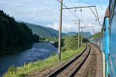 image of passenger train  - Passenger train going near the river in the Carpathian Mountains - JPG