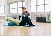 Постер, плакат: Physical Therapist Helping Elder Woman At Gym