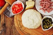 picture of food preparation tools equipment  - cooked dough and ingredients for pizza on the old wooden table - JPG