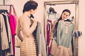 picture of showrooms  - Young woman choosing clothes in a showroom  - JPG