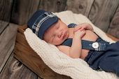 stock photo of newsboy  - An eight day old newborn baby boy wearing a blue newsboy cap suspenders and pants - JPG