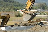 stock photo of track-hoe  - Tracked excavator loading a dump truck at a large construction site removing a hill - JPG