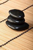 stock photo of swedish sauna  - pile of black basalt stones for thermotherapy on bamboo mat - JPG