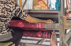 stock photo of handloom  - a woman weaving cloth with old traditional machine - JPG