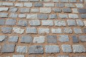 stock photo of paved road  - Gray paving slabs of natural stone torn lined in rows on the road - JPG