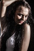 stock photo of dancing rain  - Sexy young woman dancing under the rain over black background - JPG