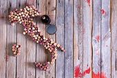 foto of bottles  - Artistic conceptual map of Italy Sardinia and Sicily made of old red and white wine bottle corks on an old rustic wooden table with a glass and bottle of red wine alongside - JPG