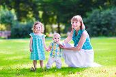 foto of little young child children girl toddler  - Beautiful young woman playing with two little children cute curly girl in a summer dress and adorable baby boy brother and sister having fun in a sunny summer park or garden - JPG