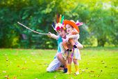 picture of horse girl  - Two happy kids laughing boy dressed as native American with colorful feather hat and little curly toddler girl in yellow boots with a toy horse playing cowboy outdoors on a sunny summer day - JPG
