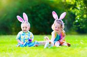 picture of baby easter  - Two little children cute curly toddler girl and funny baby boy wearing bunny ears having fun at Easter egg hunt playing with basket and toy rabbit in a sunny spring garden
