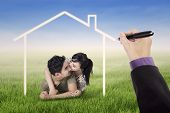 picture of dream home  - Portrait of happy couple kissing on the meadow under a dream home - JPG